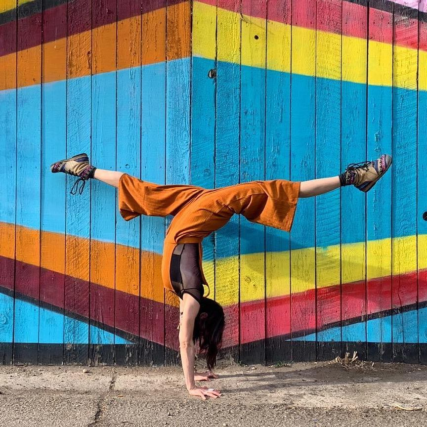Acro Teacher Christine Moonbeam in a handstand teaching online handstand conditioning